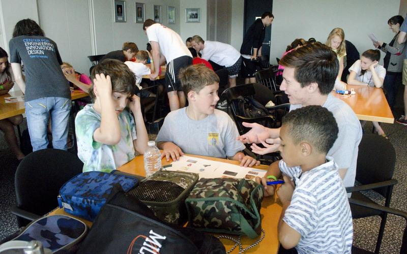 An REU student participating in an outreach activity aimed to introduce various types of research to school children.